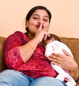 Cheerful mother gestures for us to be quiet as her baby sleeps