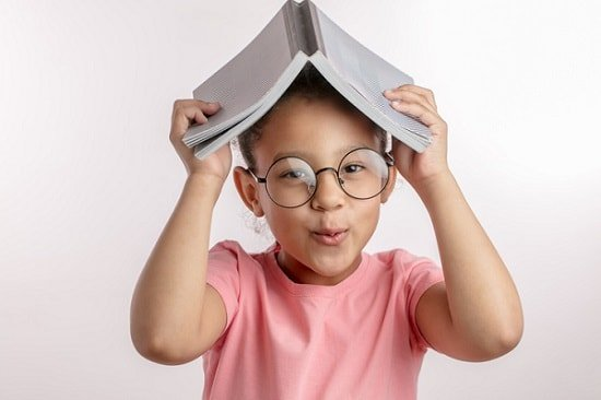 Cute girl holding book over her head - image by istock
