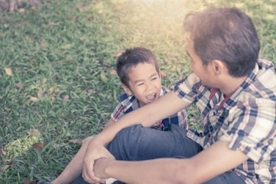 little boy cheerfully talking to his father