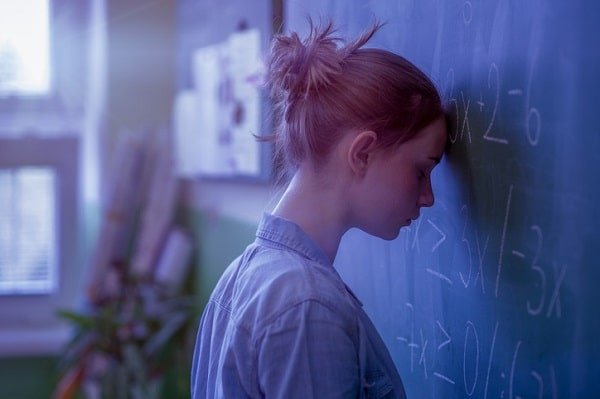 teenage girl looking defeated, pressing forehead against chalkboard with mathematical equations
