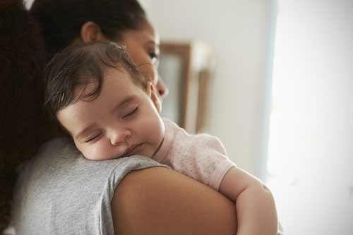 baby sleeping on mother's shoulder