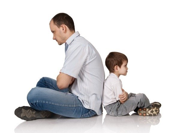 father and young son sitting back to back, in conflict, by idal / istock