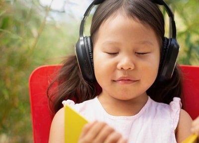 young girl listens intensely to ear phones, eyes closed
