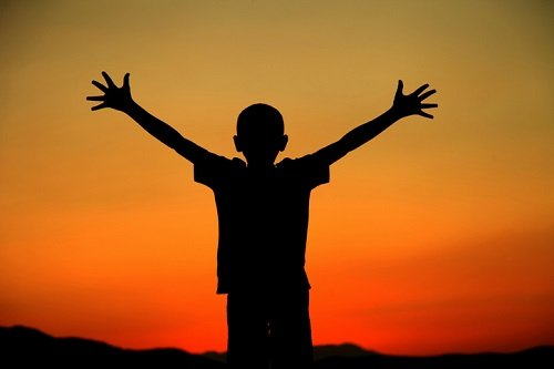 silhouette of boy with arms outstretched against a sunset - photo by bybostanci / istock