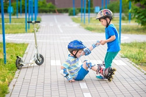 young boy helping his friend on roller skates stand up - by Pahis / istock