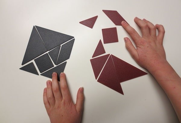 child's hands manipulating tangrams - by G. Dewar 2018