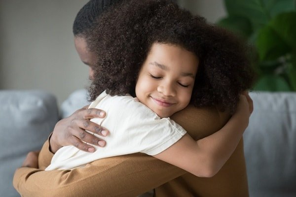 closeup of secure, happy girl hugging her father - by fizkes/istock